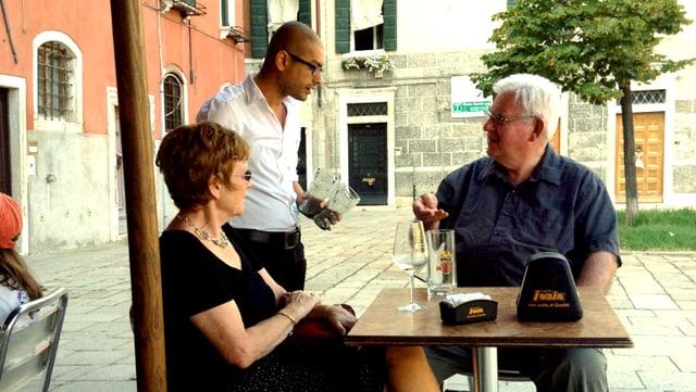 Ein Kellner in weissem Hemd bedient ein Touristenpaar.