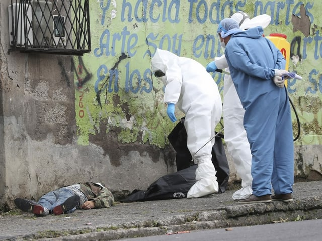 Toter liegt am Boden, daneben Personen in Schutzanzügen.