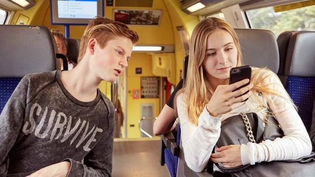 Dus giuvenils en in tren che guardan sin in telefonin.