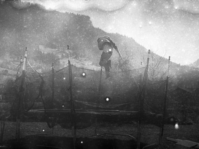 Mann hüpft auf Trampolin vor Bergkulisse.