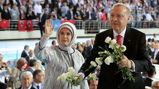 Erdogan und Frau mit Kopftuch vor Menge. Er hat Blumen in der Hand.