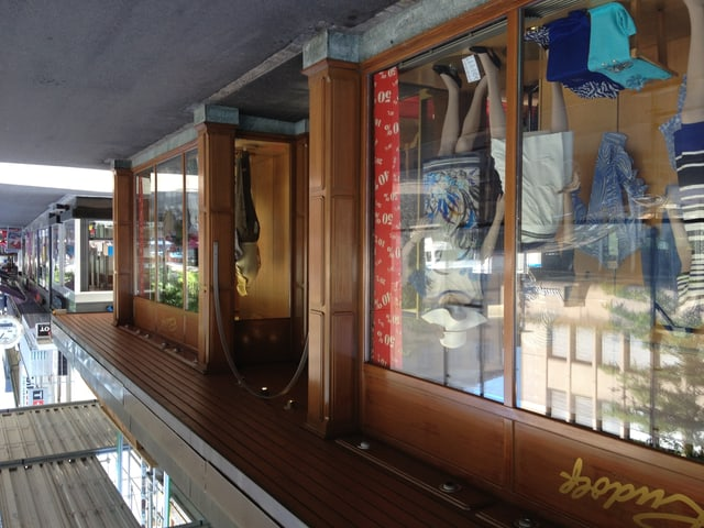 Die Ladenfront aus braunem Holz mit den Schaufenstern. Zu sehen ist ein älteres Modegeschäft.