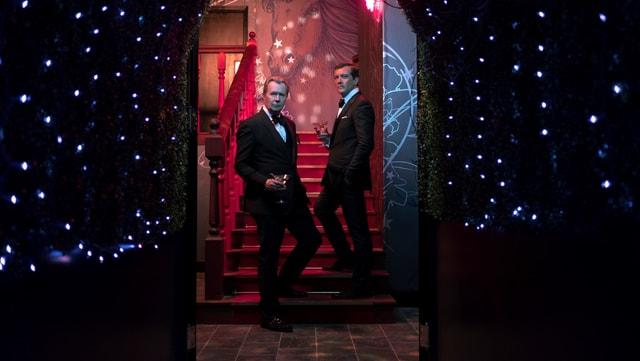 Zwei Männer, schick angezogen, stehen am Fusse einer Treppe.