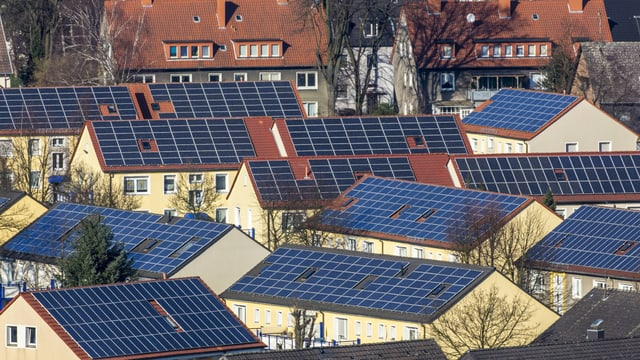 Symbolbild: Dächer von benachbarten Mehrfamilienhäusern sind alle mit Sonnenzellen bedeckt.