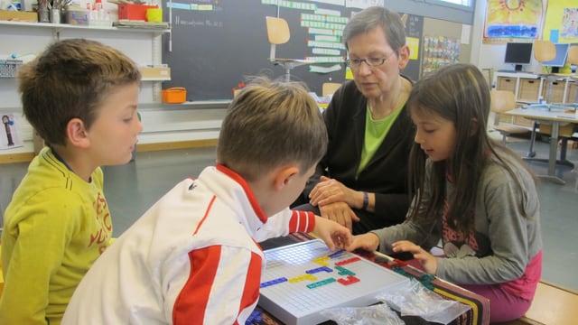 Drei Kinder und eine Seniorin beim Kreuzworträtselspiel.
