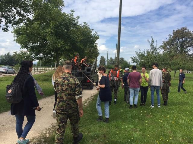 Eine Gruppe junger Läute hinter einem Armeefahrzeug.