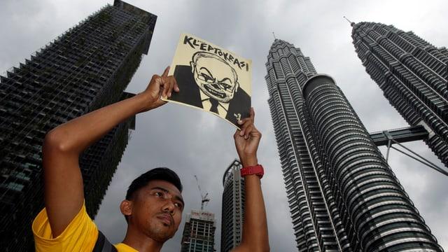 Ein Demonstrant hält einen Flyer hoch mit einer Karikatur von Najib mit der Überschrift «Kleptokratie».