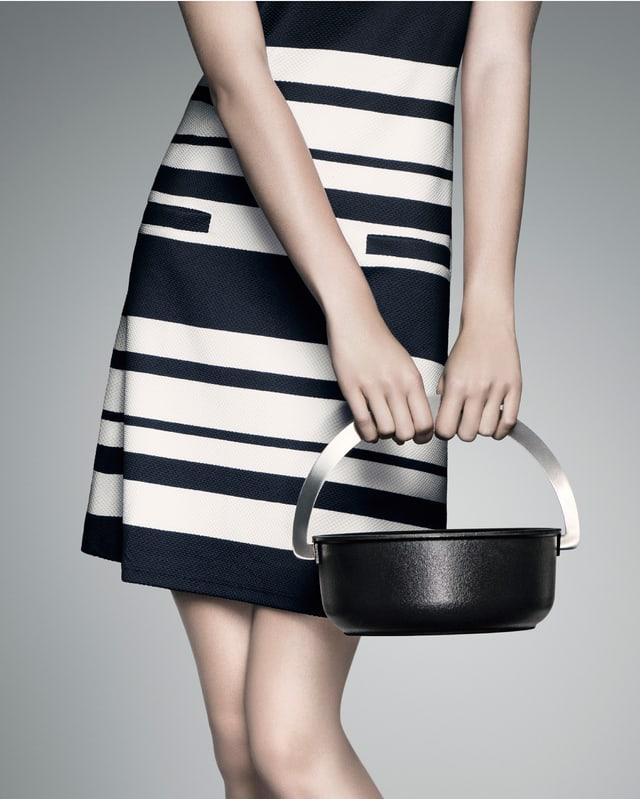 Frau in schwarz-weiss gestreiftem Kleid hält schwarze Pfanne wie eine Handtasche.