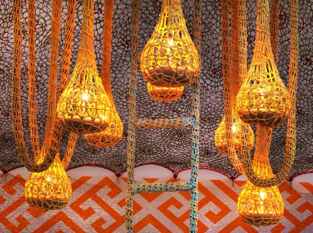Weisse Netze hängen von der Decke, gelb beleuchtet.