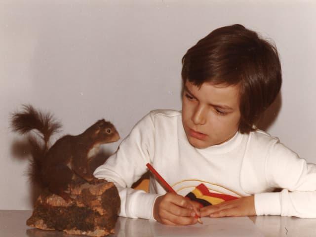 Kleiner Junge betrachtet ein ausgestopftes Eichhörnchen und macht Notizen dazu.
