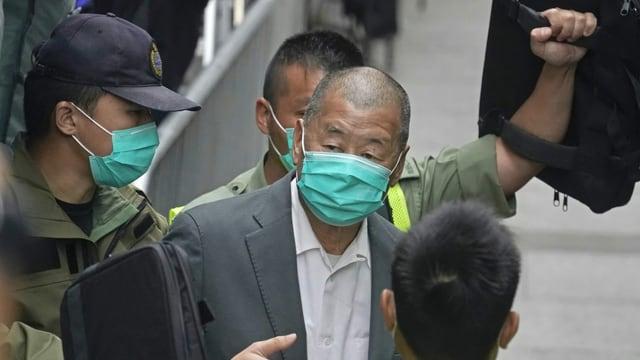 Jimmy Lai, umgeben von Polizisten.
