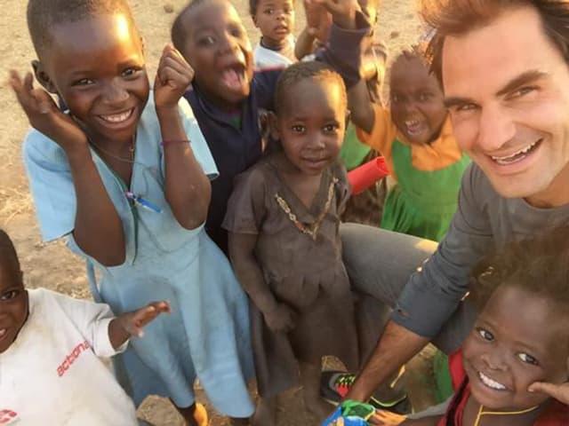 Roger Federer auf einem Bild mit sieben strahlenden maawischen Kindern