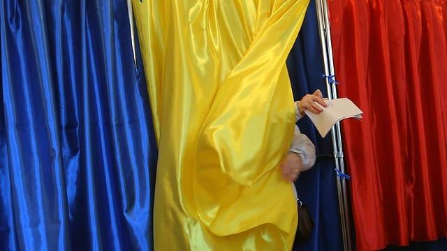 Person öffnet den in den Landesfarben gehaltenen Vorhang einer Wahlkabine.