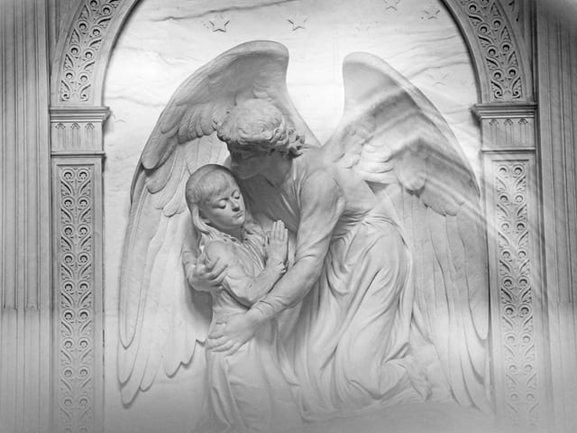 Ein weisser Engel aus Marmor umarmt ein kleines Mädchen.