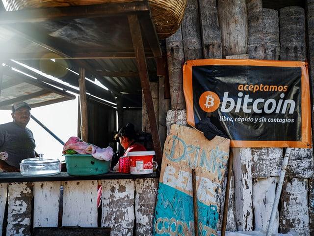 An einem Stand hängt ein Banner, worauf in spanisch steht, dass Bitcoin akzeptiert wird. Man sieht nebendran den Tresen.
