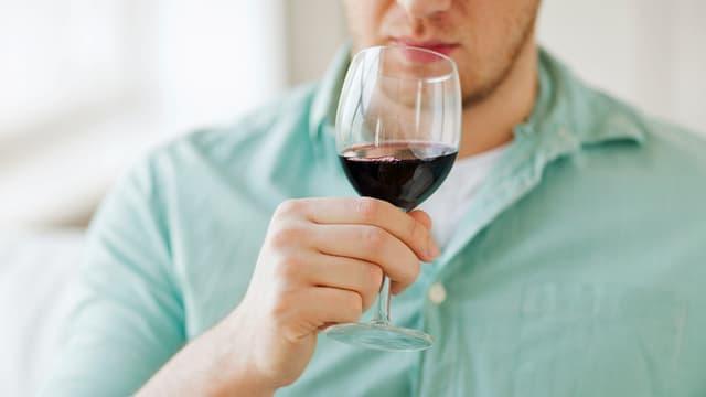 Ein Mann trinkt ein Glas Rotwein.