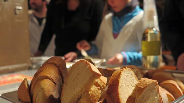 Brotkorb im Vordergrund, im Hintergrund Kind am Suppe schöpfen