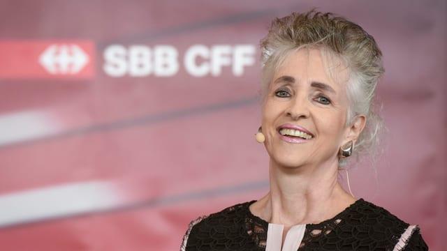 Regierungsrätin Carmen Walker Späh lachend und mit grau-meliertem Haar vor einem SBB-Logo.