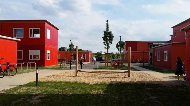 Ein Klettergerüst steht inmitten roter Container-Häuser.