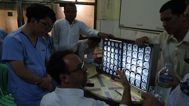 Fünf Personen sitzen und Stehen um einen Bildschirm, der Aufnahmen eines zu operierenden Schädels zeigen.