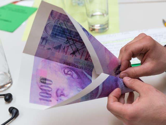 Ein Delegierter bastelt ein Papierflugzeug aus einer Kopie der Tausender-Note.
