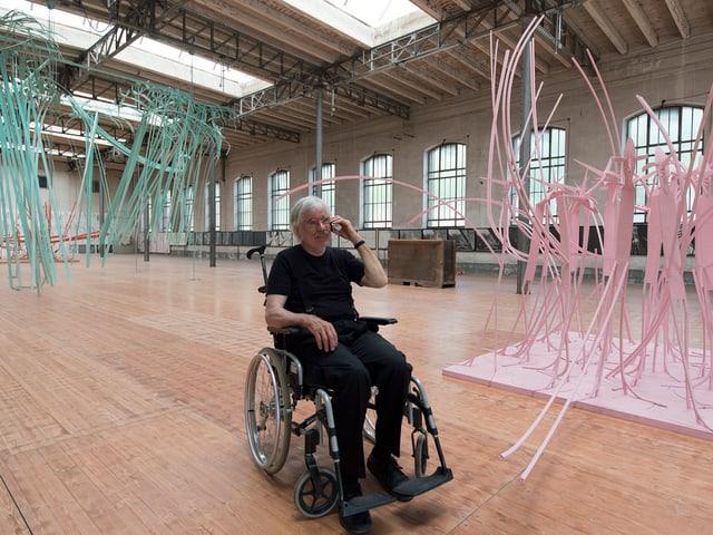Hutter sitzt im Rollstuhl in den Räumen des Tramdepots und telefoniert am Handy. Im Hintergrund seine Werke.