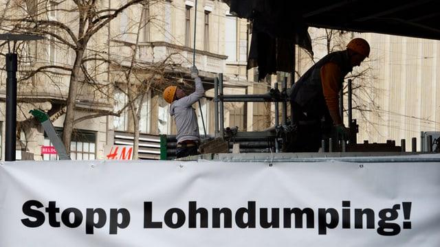 Ein Plakat mit der Aufschrift «Stopp Lohndumping», dahinter zwei Bauarbeiter bei der Arbeit.