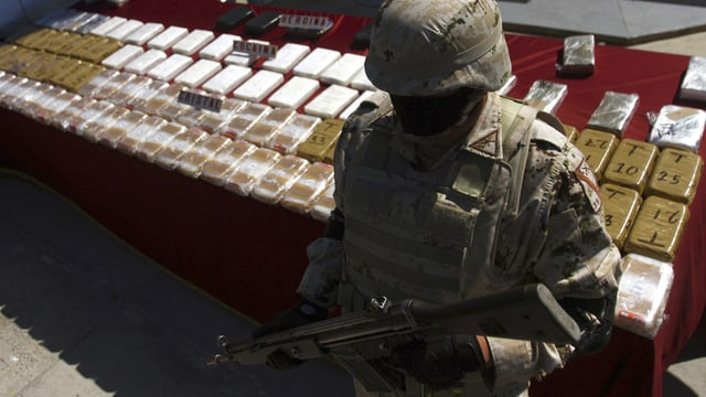 Polizist vor Drogenpaketen