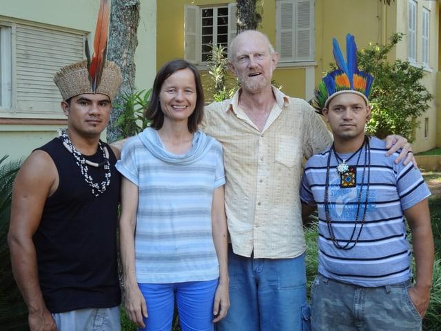 Ein Gruppenfoto mit vier Menschen, zwei tragen Federschmuck auf dem Kopf.