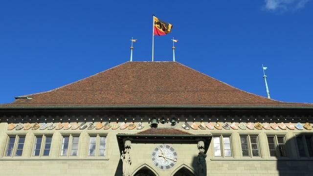 Man sieht den oberen Teil des Rathaus, auf dem Dach weht eine Berner Fahne mit dem schwarzen Bär.