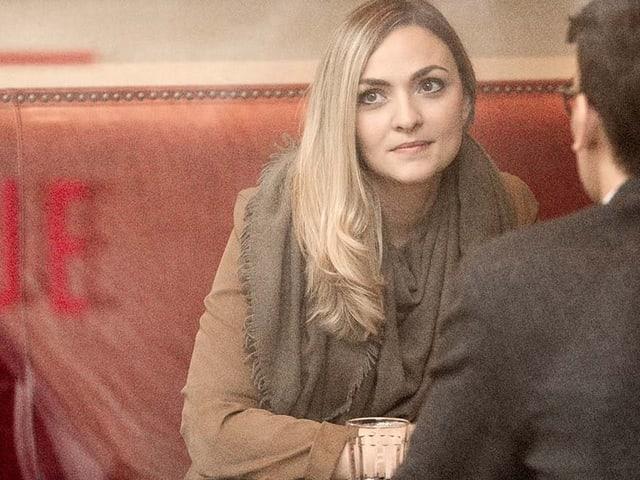 Frau sitzt gegenüber Mann auf Bank in einem Café.