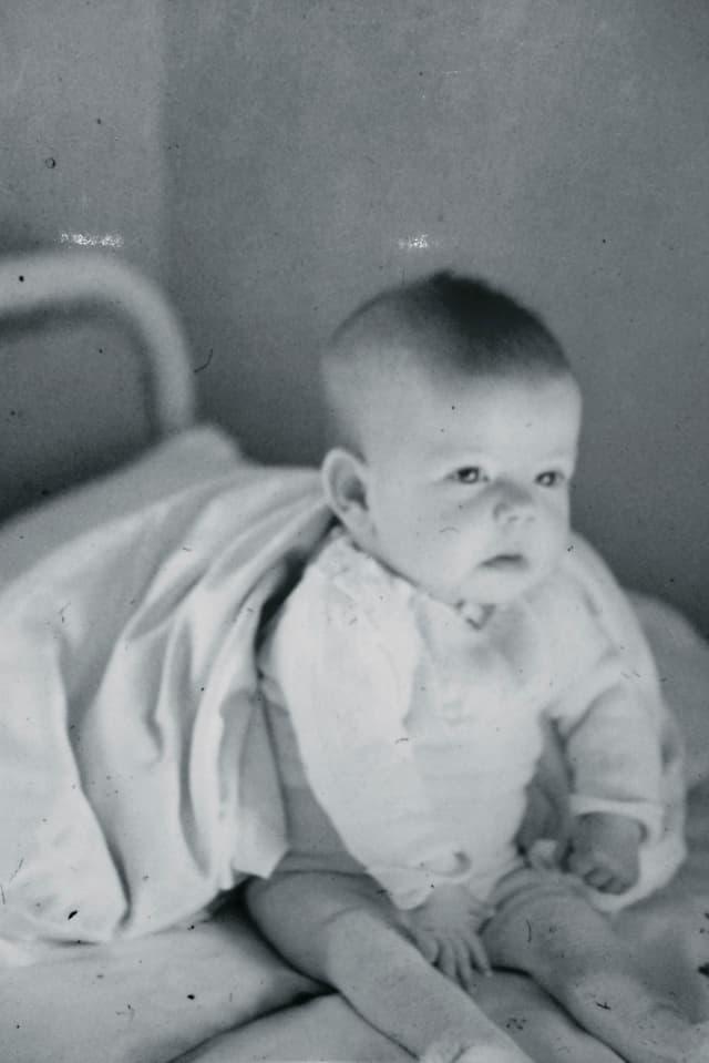 Ein Baby sitzt auf einem Bettli.