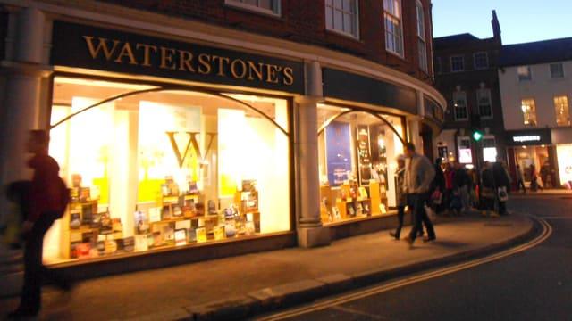Eine Waterstones Filiale in London, abends mit erleuchteten Schaufenstern.