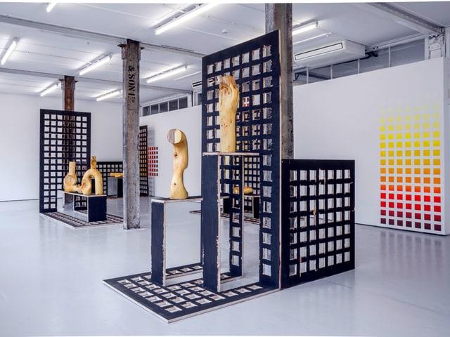 Ausstellungsraum mit gemotrischen Wandmalereien, gitterartigen Trennwänden und abstrakten Holzskulpturen.