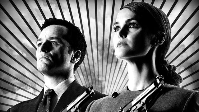 Elizabeth und Philip Jennings im Bild. Sie tragen beide eine Waffe.