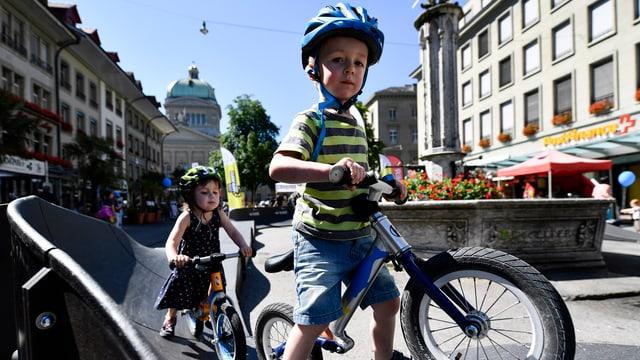 Zwei Kinder mit Helm versuchen sich auf dem Bärenplatz vor dem Bundeshaus an einem Veloparcours.