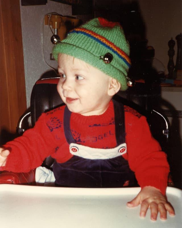 Ein kleine Bub mit grüner Mütze und rotem Pullover sitzt in einem Kindersitz an einem Tisch.