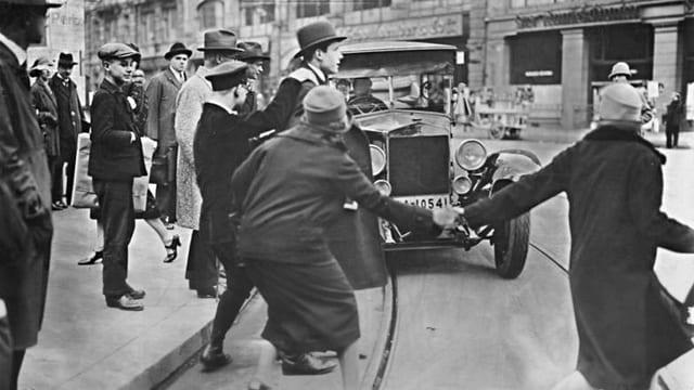 Strassenszene in Berlin um 1920: Ein Auto fährt auf eine Reihe von Fussgängern zu.
