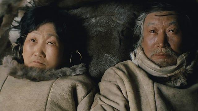 Ein Inuit Paar liegt am Boden und blickt in den Himmel.