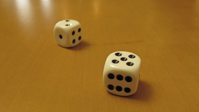 Zwei Würfel, einer mit der Zahl fünf oben, der andere mit der Zahl zwei.