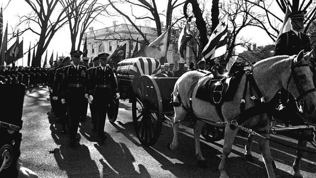 Kutsche mit Kennedys Sarg bedeckt von US-Flagge.