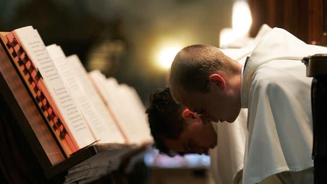 Mönche verbeugen sich vor geöffneten Büchern.