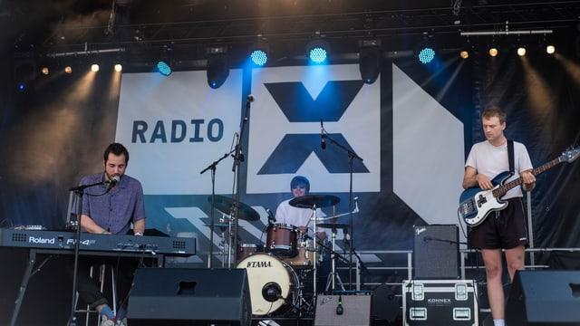 """Band auf der Bühne vor grossem """"Radio X""""-Logo."""