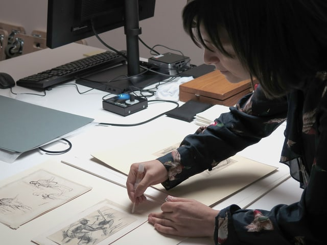 Frau entfernt mit einem Wattestäbchen Klebstoffreste von einer Zeichnung.