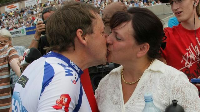 ein Rennradfahrer küsst im Trikot eine Frau
