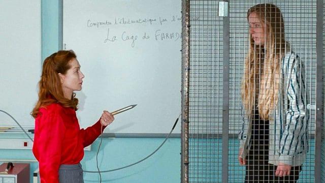 Eine Frau steht in einem Klassenzimmer. Neben ihr eine junge Frau, eingespert in einen Käfig.