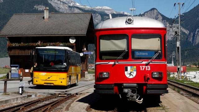 in auto da posta ed in tren da la viafier retica a la staziun da Razén.