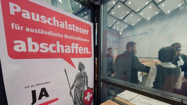 Ein Abstimmungsplakat «Pauschalsteuer für ausländische Multimillionäre abschaffen» in roter Sprechblase.