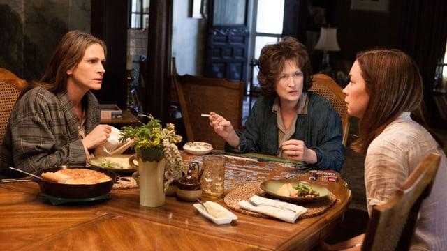 Drei Frauen sitzen am Tisch, eine raucht, die zwei anderen essen.