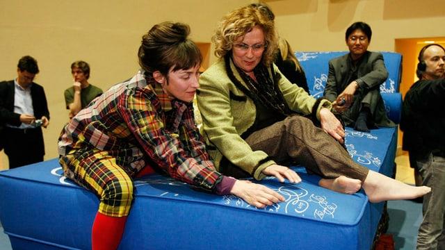 Überdimensionierte blaue Chaiselongue, darauf Eveline Hasler und Pippilotti Rist.
